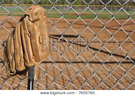 Baseball Bat and Glove Leaning Against the Backstop poster