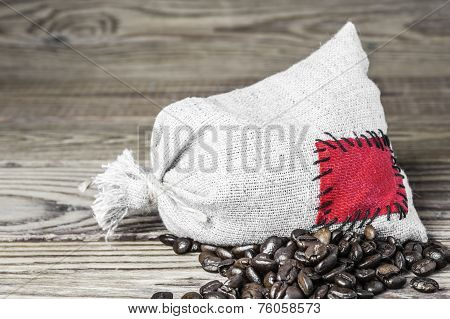 Concept of the thrift storing - Coffee beans in the burlap sack with the patch on a wooden backgroun