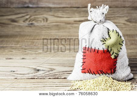 Concept of the thrift storing -Mustard seeds in the burlap sack with the patch on a wooden backgroun