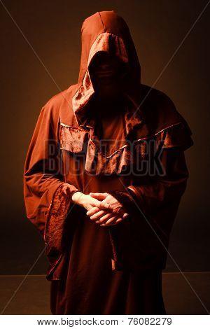 mysterious Catholic monk in twilight. studio shot poster
