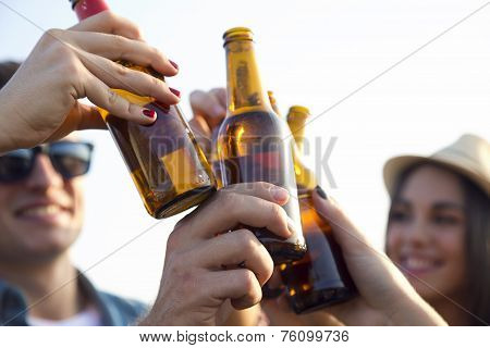Portrait Of Group Of Friends Toasting With Bottles Of Beer.