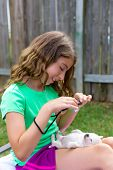Kid girl taking photos to puppy dog pet with camera in outdoor backyard poster