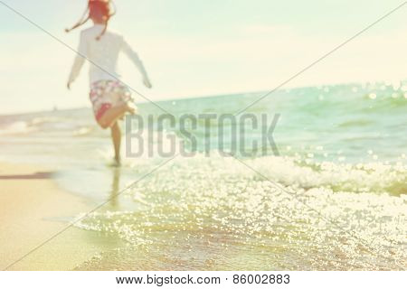 Soft image of a child running on the beach, defocused, instagram effect.