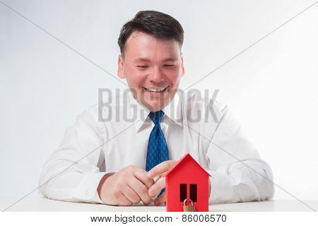 Man with a red paper house