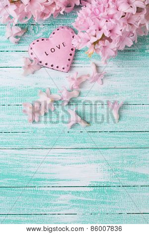 Postcard with fresh flowers hyacynths and decorative heart on turquiose painted wooden planks. Selective focus. Place for text. poster