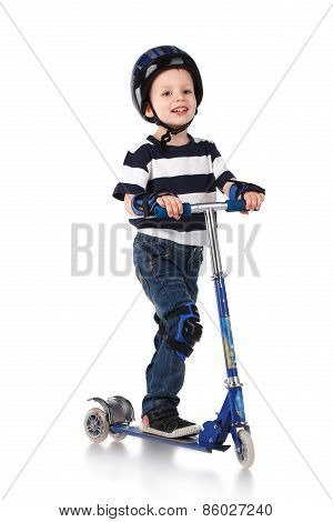 Little Boy In Protection Helmet And In The Knee And Arm Ruffles Riding His Scooter