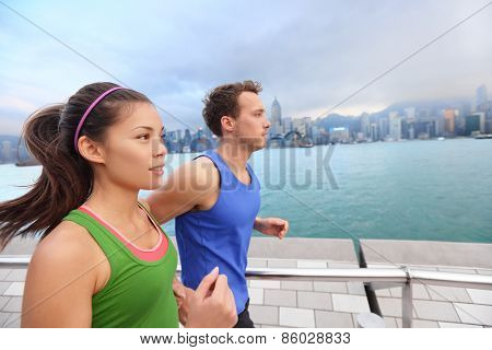 Running couple jogging in Hong Kong city. Runners training on Tsim Sha Tsui Promenade and Avenue of Stars in Victoria harbour, Kowloon, Hong Kong. Fitness runner man and sport woman model working out. poster