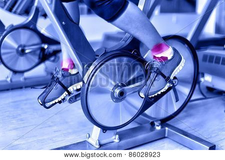 Sports injury - ankle pain during training on spinning bike at gym. Closeup of female athlete's legs using bicycle machine at fitness center in blue monochromatic filter.