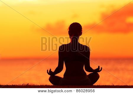 Zen yoga woman doing meditation on beach - wellness concept. Female silhouette relaxing sitting at sunset background meditating at ocean retreat. Summer orange sunrise sky.