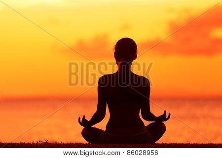 Zen yoga woman doing meditation on beach - wellness concept. Female silhouette relaxing sitting at sunset background meditating at ocean retreat. Summer orange sunrise sky.