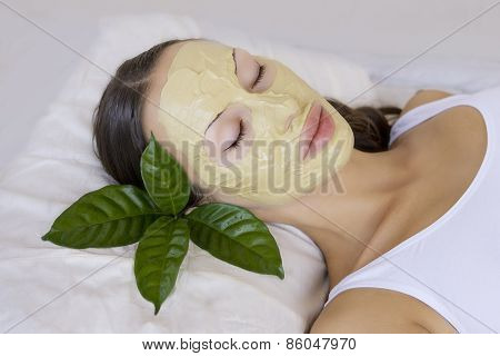 Spa Outdoor Beautiful young woman lying with natural Indian Multani Matti clay facial mask on her face skin care and wellness poster