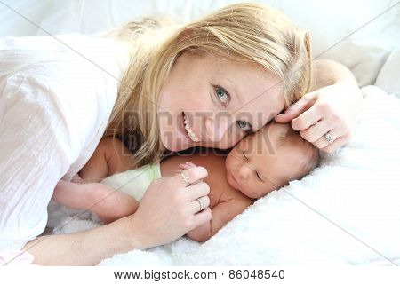 Happy Young Mother Snuggling Her Newborn Baby Girl