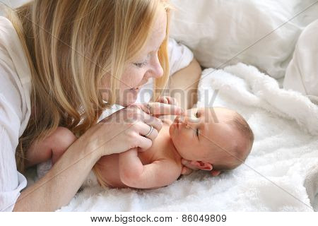 Happy Mother Touching Newborn Baby Daughters Nose
