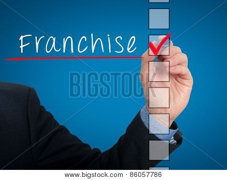 Businessman hand writing Franchise and check listing task.  Stock photo