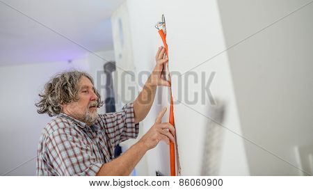 Electrician Installing Wiring In A Wall