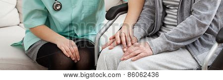 Doctor Supporting Disabled Elderly