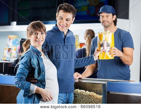 Portrait of smiling expectant couple taking popcorn from male seller at cinema concession counter