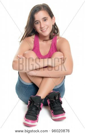 Beautiful hispanic teenage girl sitting on the floor and smiling isolated on white