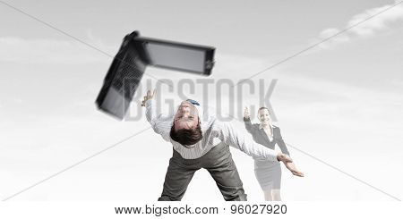 Young businessman trying to evade from thrown laptop