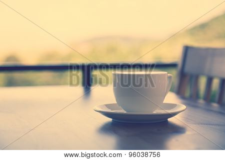 Coffee in white cup on wood table ( Filtered image processed vintage effect. )