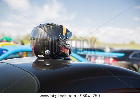 transportation, high speeds, racing and road concept - close up of car on autodrome or parking with helmet on roof top from back