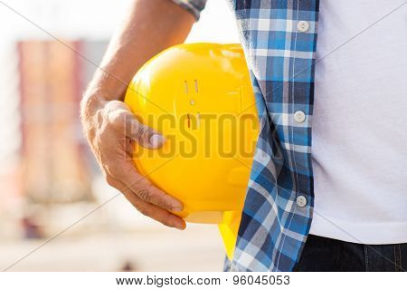 building, construction, protective gear and people concept - close up of builder hand holding yellow hardhat or helmet at construction site