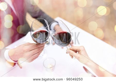 restaurant, people, celebration and holiday concept - close up of young couple with glasses of red wine at restaurant over holidays lights background