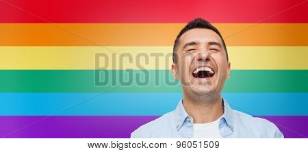 gay pride, homosexual, emotions and people concept - laughing man over rainbow flag stripes background poster