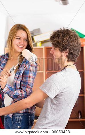 Couple renovating together as she holds up a roller with pink paint in front of his face smiling to