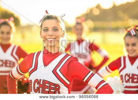 Portrait Of An Happy Young Cheerleader In Action Outdoors - Group Of Girlfriends During Cheerleading