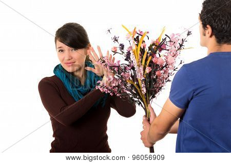 Hispanic couple fighting as man tries to give girlfriend flowers while she pushes them away with ann