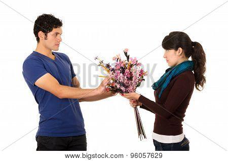 Hispanic man hesitantly receives flowers from shameful looking girlfriend