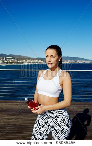 Woman with beautiful figure standing against bright sky background holding energy drink in the hand
