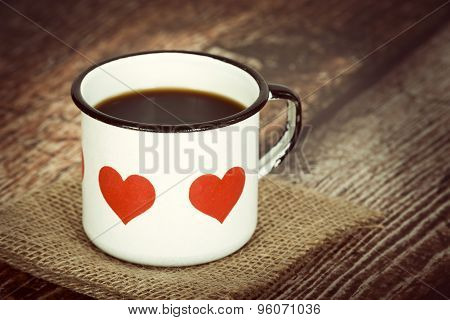 Cup Of Coffee In An Old Enamel Mug With Hearts On Vintage Background