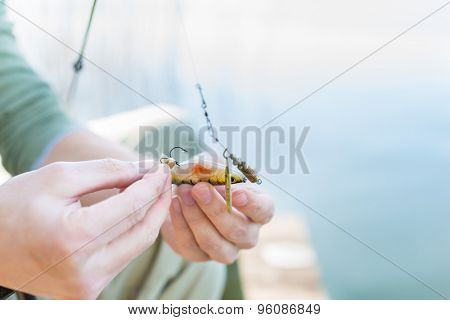 Angler fixing lure at hoof of fishing rod