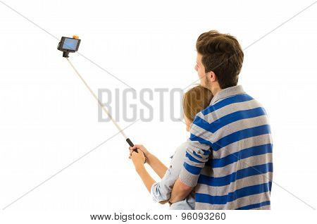 Couple with selfie stick embracing and posing for mobile shot from behind side angle