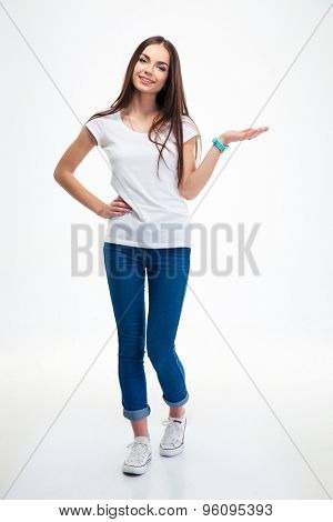 Full length portrait of a smiling woman holding copyspace on the palm isolated on a white background. Looking at camera