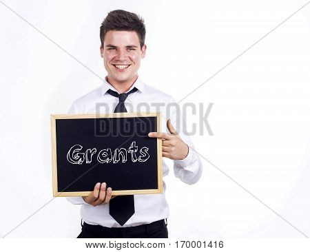 Grants - Young Smiling Businessman Holding Chalkboard With Text