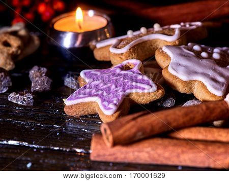 Cinnamon stick background with Christmas gingerbread man and star cookies are on wooden table and burning candles.