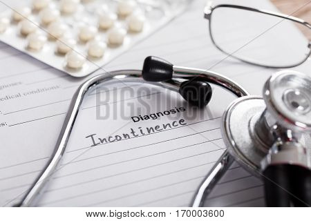 Close-up Of Diagnosis Incontinence Word And Medical Composition On Paper