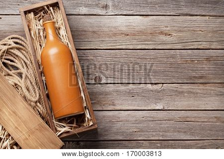 Wine bottle in box on wooden table. Top view with copy space