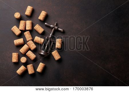 Vintage corkscrew and wine corks on stone table. Top view with copy space