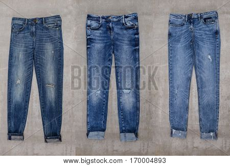 Three blue jeans trouser isolated-gray background