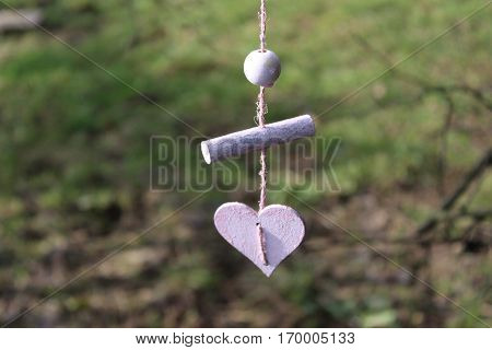 Pink wooden heart, wooden stick, wooden ball, with pink sisal cord in sunny Häselingen February 2017, in the background brown thin twigs and clay soil with partial green meadow