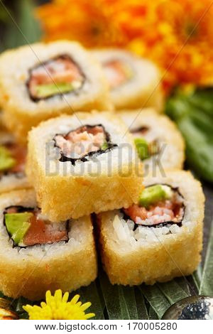 Tempura Maki Sushi - Deep Fried Sushi Roll with Salmon, Crab Meat, Avocado inside. Japanese Sushi Food and Natural Flower Concept