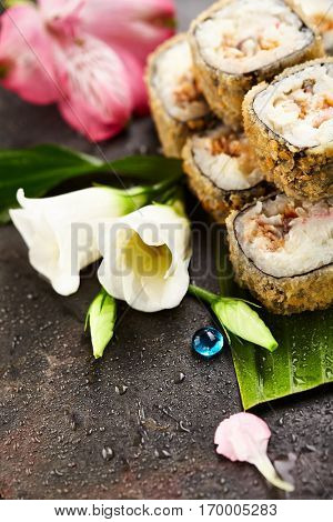Tempura Maki Sushi - Deep Fried Sushi Roll made of Shrimps, Avocado and Cream Cheese inside. Sushi Roll Served on Banana Leaf. Japanese Sushi Food and Natural Flower Concept.