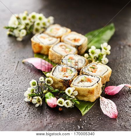 Japanese Sushi Food and Natural Flower Concept. Tempura Maki Sushi - Deep Fried Sushi Roll made of Fresh Raw Salmon, Smoked Eel, Cucumber and Cream Cheese inside. Sushi Served on Banana Leaf.