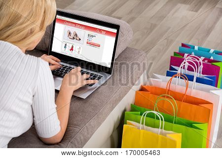 Close-up Of Woman Shopping Online Using Laptop With Colorful Shopping Bags On Floor
