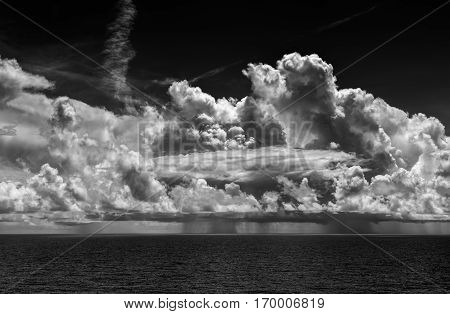 Ocean Thunderstorm with Cumulonimbus clouds and rain. A clear sky surrounds the storm with ocean water below. The photo is in black and white.