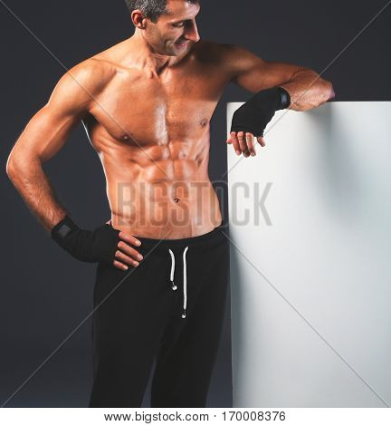 Strong athletic man standing near board on black background